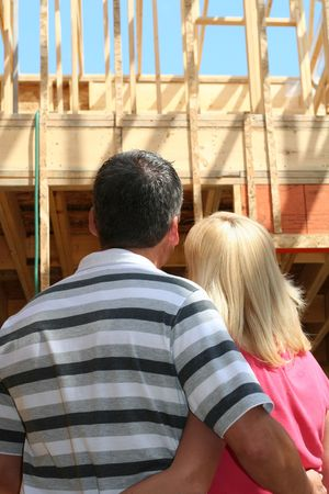 Young couple looking at their new home, still under construction.