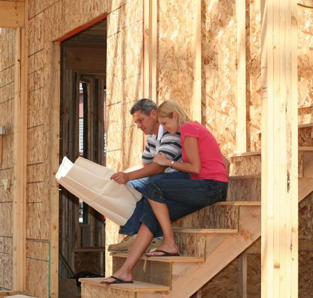 residential construction: Young couple looking at plans of their new home.  Stock Photo
