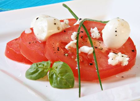 Tomato salad with bocconcini cheese and basil.  photo