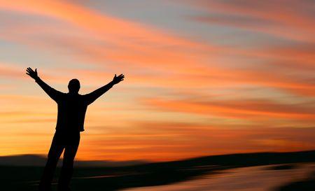 美しい夕日に直面して差し出された腕を持つ男