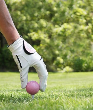 hand: Ladies hand placing a pink golf ball on a tee.