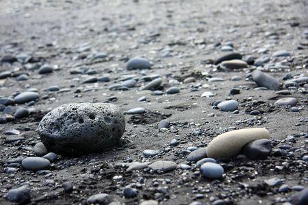 Lava rocks on a black sand beach, Iceland. Shallow dof, focus on the big rock.  Reklamní fotografie