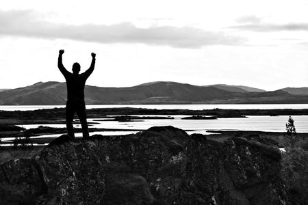 Silhouette of man with his arms stretched out to the sky.  photo