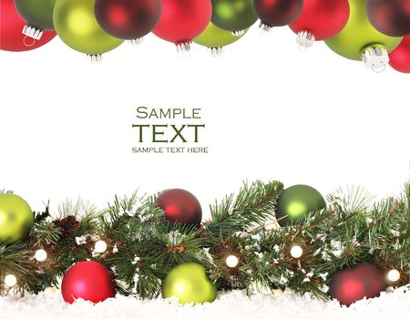 christmas decorations with white background: Christmas border of evergreen, ornaments, lights and snow.