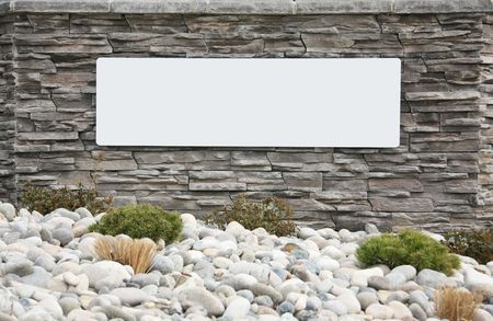 Blank sign on a brick wall at the entrance of a new subdivision. Add your own text.