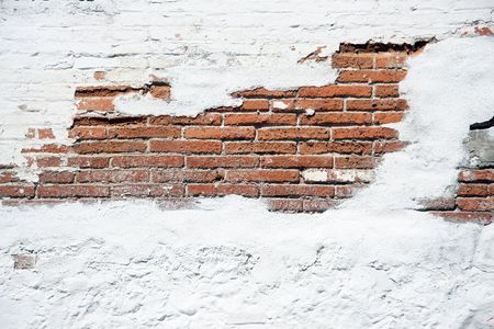 repaired: Old brick wall with worn white plaster.