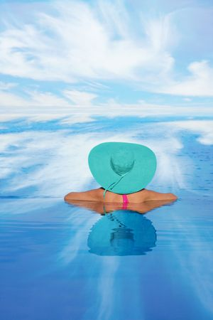 Woman in an infinity swimming pool overlooking the ocean.  Stock Photo