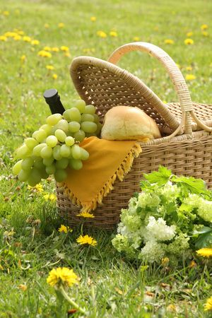 Picnic basket with bread, wine, grapes and flowers.  photo