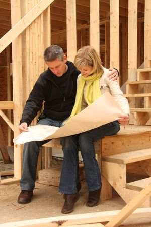 Happy paar gaan over het blauwe afdrukken van hun nieuwe huis nog in aanbouw.