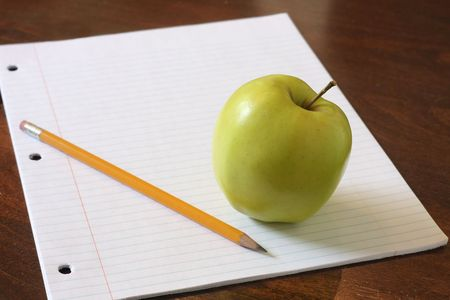 Paper, pencil and an apple for homework.