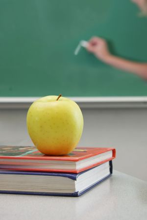 Books and apple, teacher wirting on the chalkboard. Stock Photo - 5113141