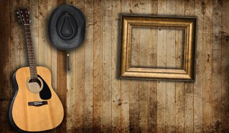 boarded: Cowboy hat, guitar and empty picture frame, against an old barn background.  Stock Photo