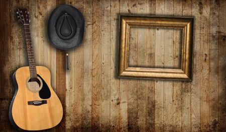 saloon: Sombrero de cowboy, la guitarra y el marco de imagen vac�a, en contra de un antiguo granero de fondo.