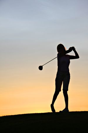 woman golf: Lady golfer swinging her driver at sunrise.