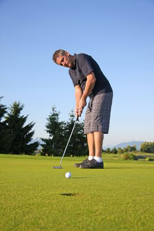 Golfer on the green putting the ball. Stock Photo - 5137526