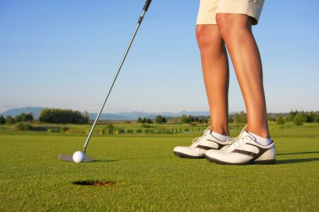 Close up of a lady golfer, putting.  Imagens