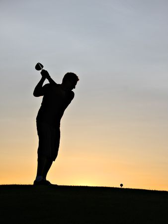 Golfer swinging his driver at sunrise. photo