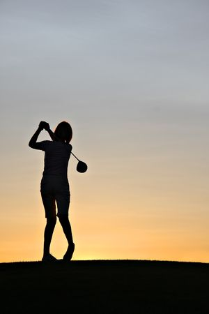 Female golfer swinging a driver at sunrise. photo