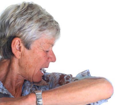 swine flue: Elderly woman sneezing into her sleeve. Stop the spread of germs! Stock Photo