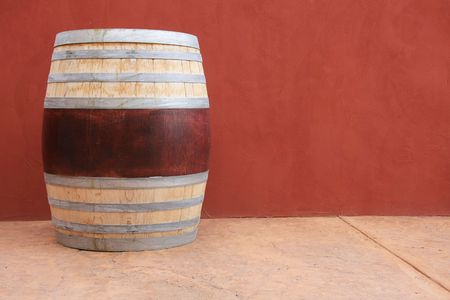 Wine barrel against a red wall.