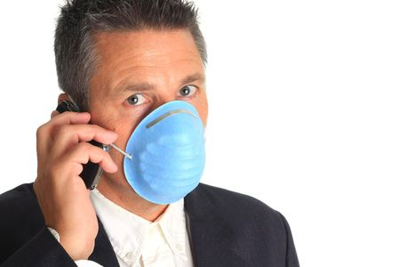 swine flue: Man on the phone while wearing a flu mask.