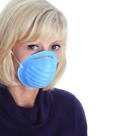 swine flu: Woman wearing a mask as protection against the influenza virus.  Stock Photo