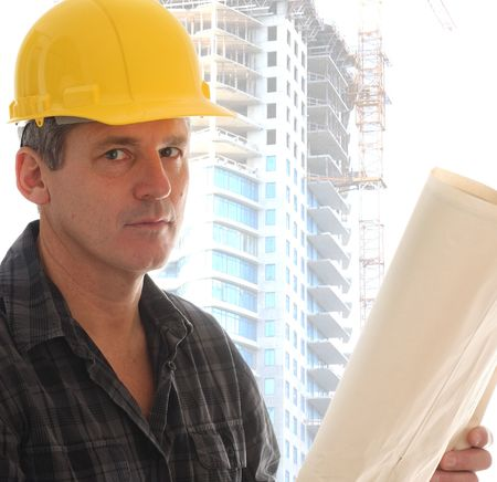 Contractor holding blue prints in front of a highrise. Stock Photo - 5948783