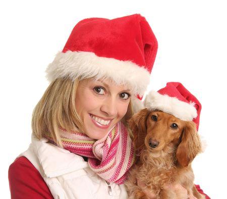 Smiling woman and cute dachshund, both wearing Santa hats.  photo