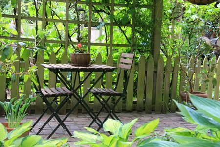planters: Patio furniture on a cozy little terrace.  Stock Photo