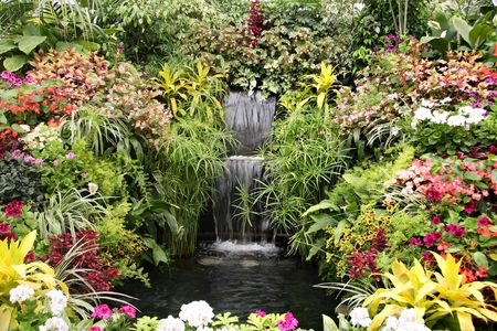 Beautiful waterfall garden surrounded by flowers.