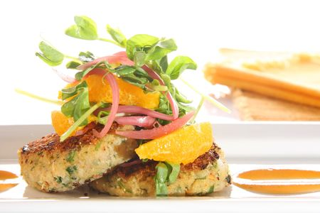 Gourmet crab cakes with grapefruit slices.