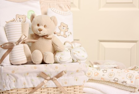 Baby gift basket including a teddy bear, sleepers, blankets and booties. Also available in vertical.  photo