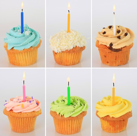 Six birthday cupcakes with lit candles.  photo