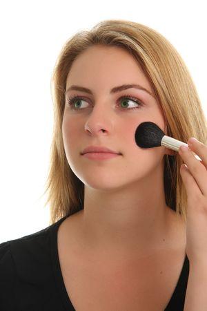 Beautiful teenage girl applying her makeup photo