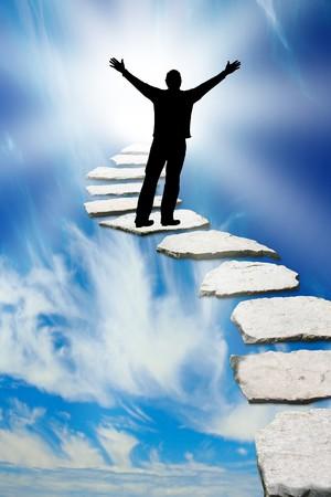 Silhouette masculine sur un Pierre chemin menant vers le ciel