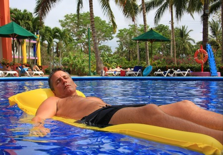 float: Man relaxing on a floating mattress in a swimming pool.