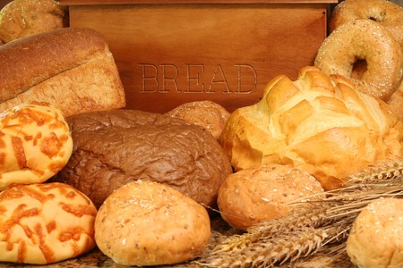 Bread box surrounded by bread and buns.  Stok Fotoğraf