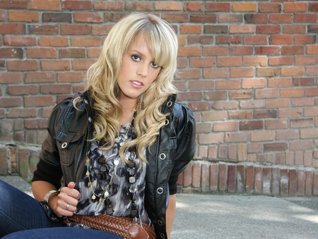 Beautiful blond woman in leather jacket against brick wall.