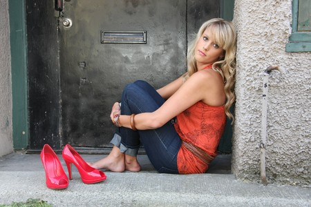 Urban portrait of a barefoot girl with high heels next to her.