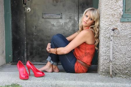 tacones rojos: Retrato urbano de una chica descalza con tacones altos junto a ella.