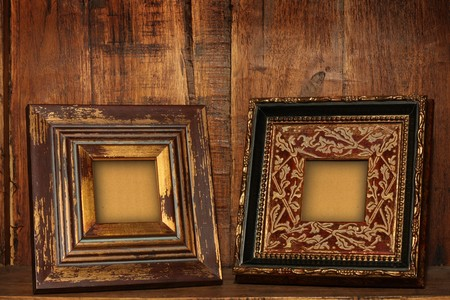Antique picture frames on an antique cabinet shelf.  photo