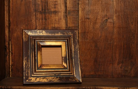 Antique picture frame in an antique wooden cabinet.  photo