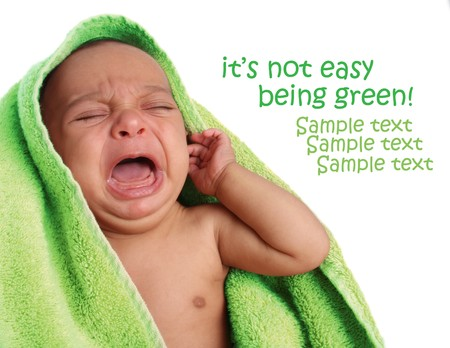 Crying newborn baby wrapped in a green towel.  Standard-Bild