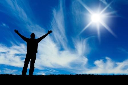 Silhouet van man met de handen verhoogd tot een heldere ster in de hemel.  Stockfoto