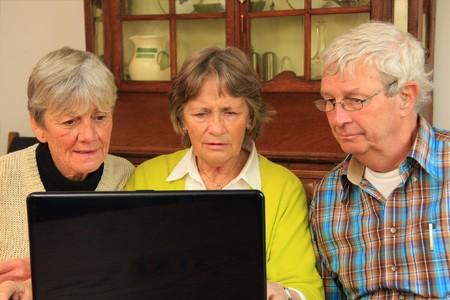 Three active senior citizens surfing the internet.  photo