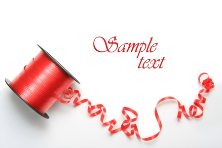 Curly red Christmas ribbon isolated on white.