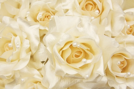 White silk roses with cream pearls. Shallow dof, focus on the center blossom.