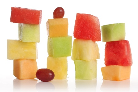 square: Sliced fruit stacks in watermelon, cantaloupe, pineapple, honeydew and grapes.