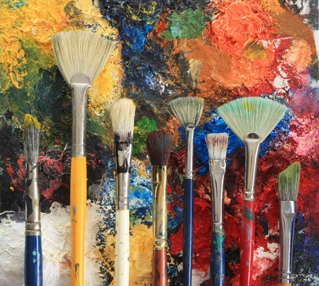 palette: Artist brushes on an oil painting background.