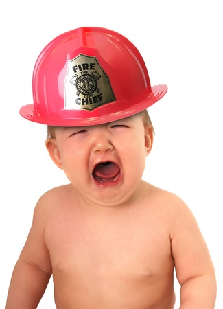 Crying baby wearing a fire fighter hat.